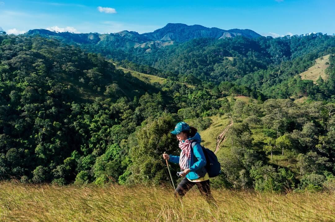 bạn nữ dùng gậy hỗ trợ trekking qua con dốc